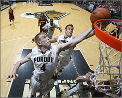 Purdue forward Robbie Hummel (4) and guard Chris Kramer sky to grab a rebound against Minnesota during the Boilermakers' 79-60 win.
