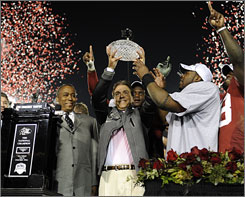Nick Saban hoists the championship trophy after his Alabama squad cut down Texas to win the BCS title.