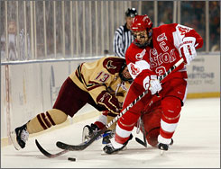 Boston University's Kevin Shattenkirk navigates the puck in front of Boston College's Cam Atkinson during the schools'  first outdoor meeting since 1920.