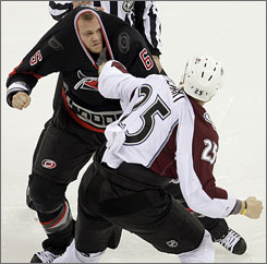 The Avalanche's Chris Stewart holds the jersey of the Hurricanes' Tim Gleason while winding up for a punch during a second-period scrum as both teams combined for 58 penalty minutes.