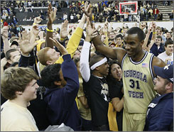 Georgia Tech's Gani Luwal is swarmed by students on the court after the Yellow Jackets' victory over visiting Duke.