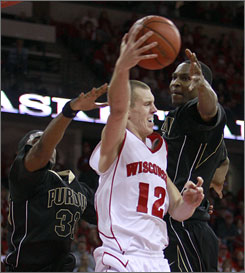 Wisconsin's Jason Bohannon (12) passes around Purdue's E'Twaun Moore, left, and JaJuan Johnson. Bohannon tied a career high with 20 points.