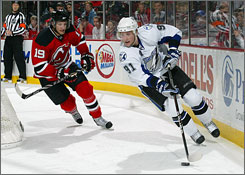 The Lightning's Steven Stamkos, skating ahead of the Devils' Travis Zajac, scored twice  once Friday and once Sunday  as Tampa Bay won the teams' suspended game.