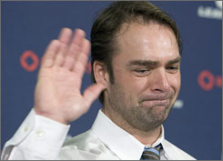 Curtis Joseph waves a tearful farewell at Tuesday's news conference announcing his retirement from the NHL.