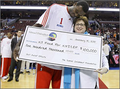 Philadelphia 76ers center and Haiti native Samuel Dalembert, left, hugs Caryl Stern, president and CEO of the U.S. Fund for UNICEF, as he presents her with a check for $100,000 to aid relief efforts in his home country before an NBA game against the Sacramento Kings.