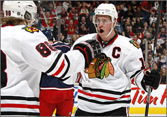 Jonathan Toews, right, celebrates one of his two goals with teammate Patrick Kane during Chicago's victory over Columbus.