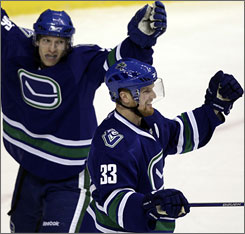 Vancouver's Henrik Sedin, front, scored the tying goal and made two assists as the Canucks crushed the Penguins.