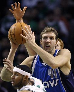 Mavericks forward Dirk Nowitzki tries to pass the ball as he is pressured by Celtics guard Eddie House, front, and forward Brian Scalabrine, rear, during the second quarter.