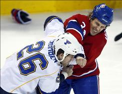 The Canadiens' Travis Moen, right, and the Blues' B.J. Crombeen duke it out in Montreal Wednesday night.