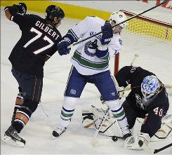 The Oilers' Tom Gilbert battles the Vancouver Canucks' Alex Burrows in front of Oilers goalie Devan Dubnyk during the first period in Edmonton Wednesday night.