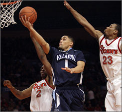 Villanova's Scottie Reynolds drives to the hoop in between St. John's Anthony Mason Jr. (2) and Paris Horne during the fourth-ranked Wildcats victory Saturday in New York.