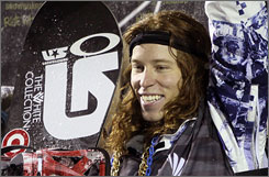 Shaun White smiles on the podium and waves to the crowd after winning Friday night at the U.S. Snowboarding Grand Prix.
