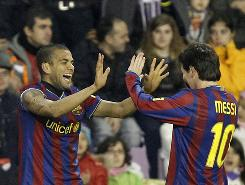 Dani Alves celebrates with Lionel Messi after scoring a goal Saturday.