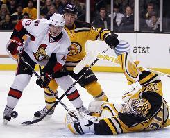 Boston goaltender Tim Thomas, right, deflects a shot by Ottawa's Peter Regin.