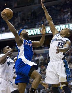 The Los Angeles Clippers' Baron Davis, center, shoots between the Washington Wizards' Caron Butler, right, and Antawn Jamison, left, during the first period of Sunday's game. Davis had 11 points and 11 assists as the Clippers snapped an eight-game road losing streak and won their 20th game, one more than last season's total.