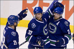 The Canucks' Aaron Rome, left, and Daniel Sedin, right, celebrate teammate Henrik Sedin's second-period goal as Vancouver improved to 9-1-0 against Eastern Conference opponents.
