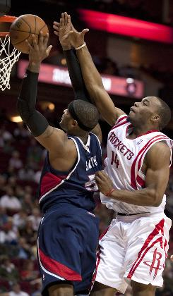 The Houston Rockets' Carl Landry fouls the Atlanta Hawks' Josh Smith during the fourth quarter on Monday. The Hawks got their first victory in Houston since 1999.