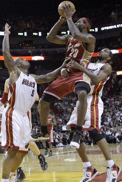 LeBron James shoots as Udonis Haslem, right, and Quentin Richardson defend in the second quarter. James hit two freethrows with 4.1 seconds left in the game to secure the victory over the Heat.