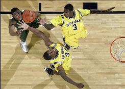 Michigan State forward Raymar Morgan, left, watches Michigan forward DeShawn Sims, bottom, and guard Manny Harris reach for a rebound in the first half Tuesday night in Ann Arbor, Mich.