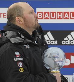 Steven Holcomb follows the U.S. national anthem during the World Cup winner ceremony Sunday in Igls, Austria.