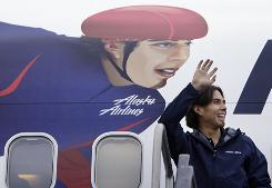 Apolo Ohno waves next to his likeness painted on the side of an Alaska Airlines plane Nov. 17, 2009, at Seattle-Tacoma International Airport.