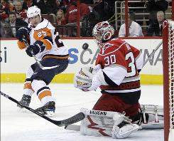 Carolina Hurricanes goalie Cam Ward deflects a shot by the Islanders' Andy Sutton during the first period Thursday night. Ward recorded 26 saves.