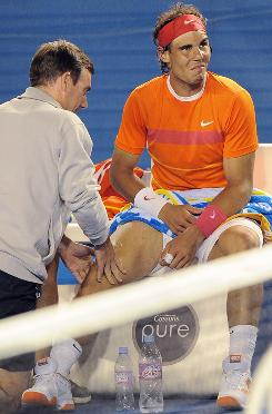 A courtside trainer checks Rafael Nadal's sore right knee during Nadal's quarterfinal match against Andy Murray at the Australian Open. Nadal retired because of the knee.