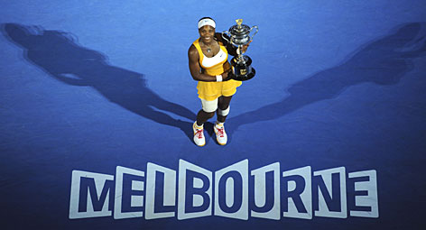Serena Williams holds the Australian Open women's singles trophy after her three-set victory over Justine Henin. The title was Williams' fifth Down Under.