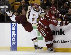 Boston College's Matt Lombardi sidesteps a check by Harvard's Tommy Atkinson during the second period of a Beanpot college hockey tournament. The Beanpot faces off the four Boston-area college hockey teams during the first two Mondays in February.