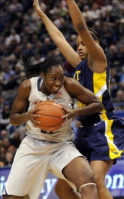 Connecticut's Tina Charles goes under West Virginia's Asya Bussie for a shot in the first half. Charles finished with 14 points and six blocks.