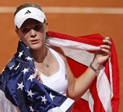 Melanie Oudin celebrates with the American flag after defeating Julie Coin of France during their first-round Fed Cup tie on Sunday in Lievin, France.