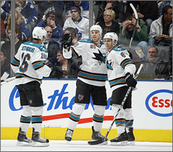 Rayne Clowe, flanked by Devon Setoguchi, left, and Joe Pavelski, celebrates his game-winning goal for the Sharks in Toronto.