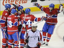 Montreal Canadiens players celebrate a goal scored against the Washington Capitals by Tomas Plekanec (14) as Alexander Ovechkin, foreground, skates away. The Canadiens snapped the Capitals' 14-game winning streak, 6-5 in overtime.
