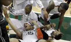 Miami center Julian Gamble, bottom left, celebrates after James Dews, lower right, made the game-winning shot to defeat Georgia Tech 64-62 Wednesday night.