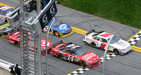 Kasey Kahne (9) passes the finish line just ahead of Tony Stewart at the end of the second Gatorade Duel qualifying race at Daytona International Speedway.