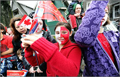 Fans lined the streets of Vancouver to welcome the Olympic torch to the city of the Games on Friday.