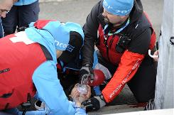 Georgian luge hopeful Nodar Kumaritashvili gets assistance from medical personnel after crashing during a luge practice run on Friday at the Whistler Sliding Center.