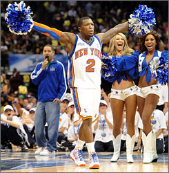 Nate Robinson gets an assist from the Dallas Cowboys cheerleaders after completing a final-round dunk.