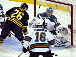 Sharks goalie Evgeni Nabokov, right, makes a save on Buffalo Sabres left winger Thomas Vanek (26) during the first period, Vanek later beat Nabokov with a second-period goal to lead the Sabres to a 3-1 win.