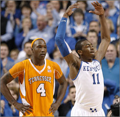 Kentucky's John Wall celebrates in front of Tennessee's Wayne Chism during the second half. Wall scored 24 points as the Wildcats prevailed.