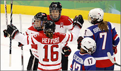 Jayna Hefford, Caroline Ouelette (back) and Meghan Acosta celebrate a second-period goal in Canada's 18-0 rout of Slovakia.