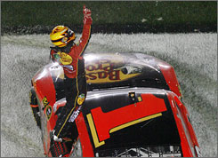 Jamie McMurray points skyward after exiting his No. 1 Chevy in the infield grass at Daytona International Speedway.