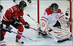 Canada's Gillian Apps scores past Swiss goalie Florence Schelling Monday.