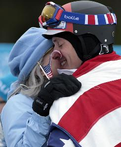Seth Wescott hugs his mother, Margaret Gould Wescott, after winning the gold medal in the finals of the mens snowboard cross event at Cypress Mountain on Monday. Wescott draped his grandfather's World War II flag over his shoulders.