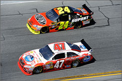 Marcos Ambrose (47) races to the inside of Jeff Gordon in the early stages of the season-opening Daytona 500.