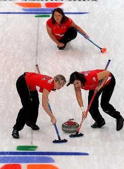 Nicole Joraanstad, left, and Natalie Nicholson of the U.S. sweep the ice for a release by skip Debbie McCormick during the women's curling round robin game against Japan Tuesday. The U.S. team dropped its opener.