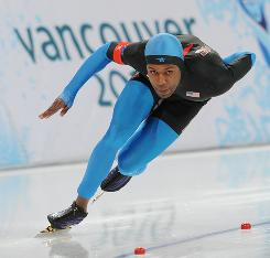 Shani Davis rounds the curve on his way to speedskating gold Wednesday at the Richmond Olympic Oval. Davis became the first man to win two gold medals in the 1,000 meters.