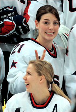 Hilary Knight clowns around behind Jenny Potter, her linemate and roommate, before the team photo is taken.