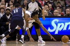 The Raptors' Chris Bosh, right, scrambles with the Grizzlies' Mike Conley for a loose ball during the first half Wednesday night. Bosh scored 32 points.
