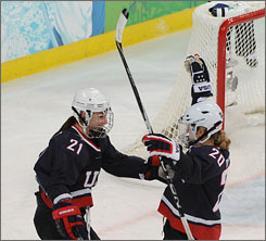 Natalie Darwitz, left, congratulates Hilary Knight's goal. Darwitz set it up and has set a U.S. record for points in an Olympic women's hockey tournament.